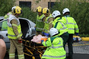 Northamptonshire Fire and Rescue Service pictured assisting the staged incident at the university where the back-seat 'passenger', played by an actor, was stretchered into the back of an EMAS ambulance.