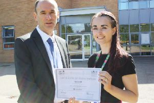 Miss Old pictured with her certificate of accreditation from the United Nations.