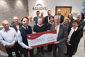 Chris Willmott from The Myton Hospices (front, left) receives a cheque for 1,000 from Alistair Clark of AC Lloyd Homes (front, right) watched by staff at its headquarters in Warwick