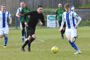 Callum Saunders brings the ball out of defence.