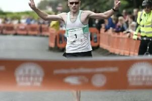 Bognor Prom 10k winner James Baker about to break the tape / Picture by Liz Pearce