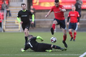 Glenn Irwin is tackled by Gary Dunlop in the charity football match at Seaview.