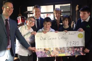 Richard Hopton, general manager at Hilton Avisford Park, and Philippa Redwood, his PA and a foundation champion, presenting the grant to staff and pupils at Oak Grove College