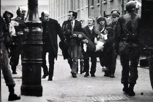 Father Edward Daly and others try to get medical aid for one of those shot by the Parachute Regiment on Bloody Sunday. 'Stanley Matchett