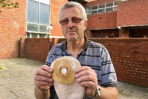 John McCartney, 70, from Boundary Road, Lancing, holding one of his catheter bags and flanges outside the place that he parked in Chatsworth Road, Worthing, behind the wall