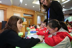 Melanie Squires, left, and Michelle Cannon working with children in Shanghai