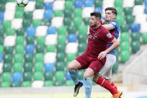 Institute striker Joe McCready shields the ball from Linfield's Jimmy Callacher during today's game at Windsor Park.