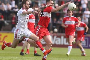 Derry's Ryan Bell tries to escape the clutches of Tyrone's Ronan mcNamee in Healy Park.
