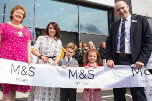 Launching the new M&S store in Carrickfergus is R_L Mayor of Mid and East Antrim Borough Council, Councillor Maureen Morrow, store manager Grace Lough and head of region for M&S Simon Layton. Helping to cut the ribbon is Eva Morrison (5) and Oscar Millar (6) from Carrickfergus Model Primary School who were the lucky winners of a colouring competition.