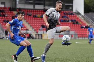 Institute's Aaron Jarvis wins the ball ahead of Dungannon Swifts player Oisin Smyth. DER3319-143KM